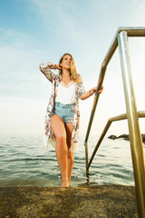 Young beautiful woman standing in a sea water and posinYoung beautiful woman standing in a sea water and posing for a camera on a sunny dayg for a camera in a sunny day