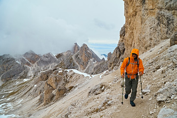 Hiker on dirt track on mountain side, Canazei, Trentino-Alto Adige, Italy