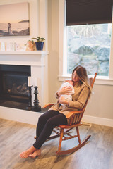 Mother sitting in rocking chair holding newborn baby boy