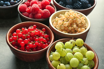 Bowls with various ripe berries on table