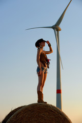 A young woman dressed as a cowgirl pauses on a  hay bale and enjoys the sunset and the new way of getting alternative energy from power windmills that stand behind her in the distance.