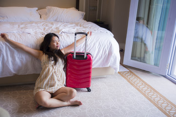 portrait of young happy and beautiful Asian Korean tourist woman with travel suitcase arriving tired at five star hotel staring the room excited