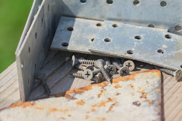 close up of construction instruments- metal corners, screws on wooden work bench outdoors