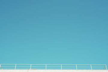 Imagen minimalista de un balcón, azotea con una valla blanca bajo un cielo azul despejado
