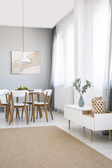 White chairs at dining table in scandi flat interior with cupboard, poster and carpet. Real photo