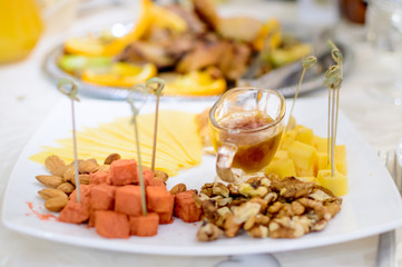 Honey, nuts and cheese nicely lie on a plate. Table setting.