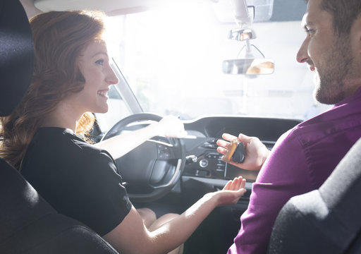 Happy car dealer giving keys to smiling woman during test drive