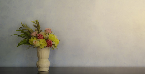 Fresh pink, yellow, red  flowers bouquet on shelf in front of wooden wall. View with copy space.