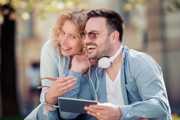 Romantic couple sharing headphones outdoor