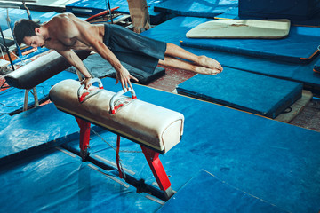 Photo Blinds Gymnastics The sportsman during difficult exercise, sports gymnastics
