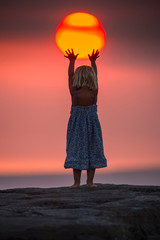 Young girl reaching up to touch setting sun, rear view, false perspective, Doolin, Clare, Ireland