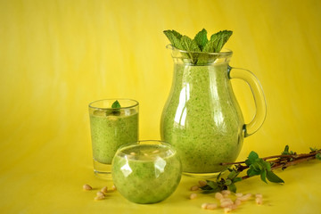 Green smoothie in glass vessels against the yellow background