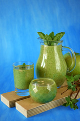 Green smoothie in glass vessels against the blue background