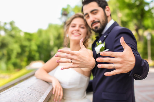 Happy newlyweds showing their wedding rings outdoors