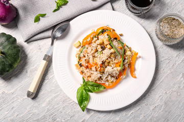Plate of tasty rice with vegetables on table