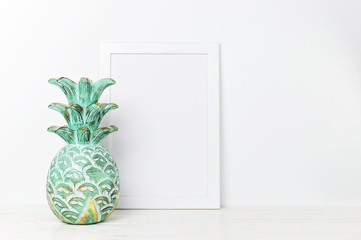 Wooden empty frames for a photo and wooden emerald pineapple on a background of a white wall. Blank paper frames, modern home decor mock-up. Interior accessories, home decor elements.