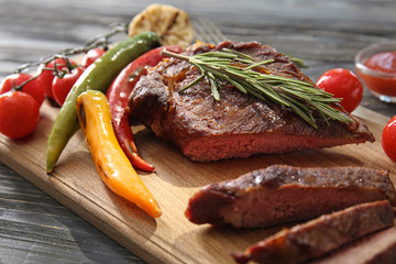 Canvas Prints Board with tasty cut grilled meat, vegetables and herbs on wooden table
