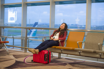 young pretty tired and exhausted Asian Korean tourist woman in airport sleeping bored sitting at boarding gate hall waiting for delayed or canceled flight
