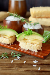 Sandwiches with cheese and avocado slices on pieces of rice gluten free bread