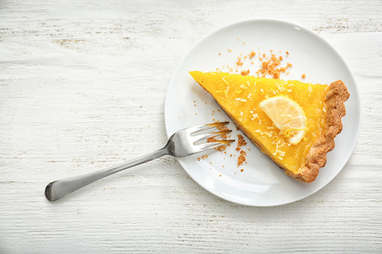 Plate with piece of tasty lemon pie on white wooden table