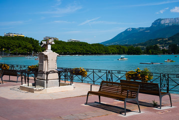 Annecy lake riverbank with bench and sundial and Veyrier mount of Alps mountains in background