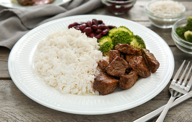Tasty boiled rice with meat and vegetables on plate