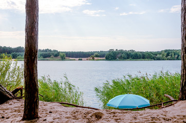 Summer lake with blue parasol