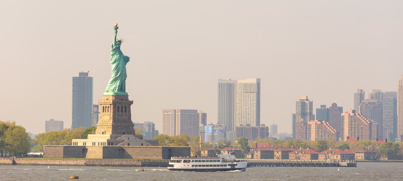 Statue of Liberty with Liberty State Park and Jersey City skyscrapers in background, USA.