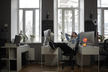 A man thinking of a vacation in a modern office while relaxing