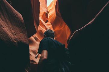 Traveller walking between colorful rocks, Antelope Canyon, Navajo Tribal Park, Arizona, USA