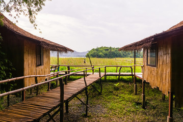 Bamboo hut and bamboo bridge with the glass green field and mountain background