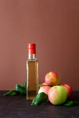 Apple vinegar in glass bottle and fresh apples on brown wooden desk