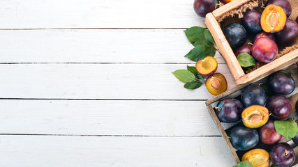 Plums with leaves in a wooden box. On a white wooden background. Top view. Free space for your text.