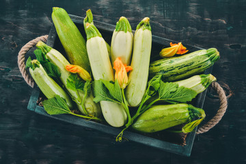 Squash Marrow zucchini in a wooden box on a black table. Top view. Copy space.
