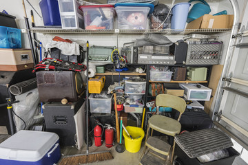 Messy cluttered junk filled suburban garage shelves with vintage electronics and sports equipment.