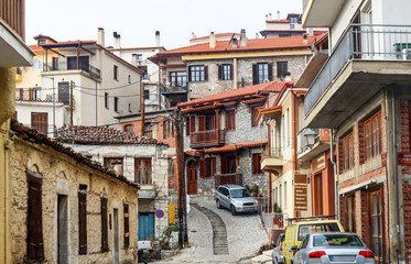 A view of buildings and alleyways and a tangle of electric lines in the mountain town of Delphi Greece