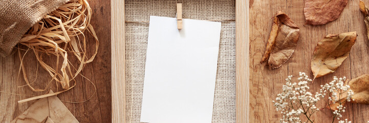 Panoramic mockup frame with white flowers in a vase with old envelopes, a leaf and a jute bag