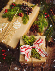 Christmas gift wrapped in kraft paper with decoration on a rustic wooden background from above. Flat style. mockup free space. Blank form