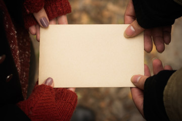 Couple holding an empty vintage sheet of paper in their hands