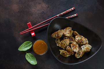 Bowl of fried korean wontons with sesame seeds over brown metal background, top view, horizontal shot