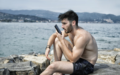 Athletic shirtless young man at the seaside using cell phone to send a voice message, with the sea behind him