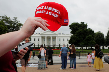 "A tourist holds a ""Make America Great Again"" hat outside the White House in Washington"