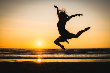 Silhouette of a happy beautiful dancer girl at sunset
