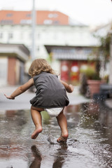 Kind Mädchen läuft und fällt in Wasser Pfütze. Blond child falling in puddle water.