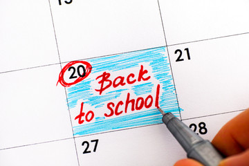 Woman fingers with pen writing reminder Back to School in calendar.