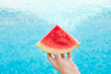Young Woman Holds in Hand Wedge Slice of Juicy Watermelon by Swimming Pool. Blue water. Sunlight. Vacation Relaxation Wanderlust Summer Vibes. Authentic Atmosphere. Lifestyle. Poster with Copy Space