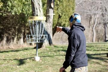 Disc golf putt into basket