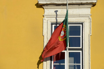Portuguese flag over the window and yellow wall