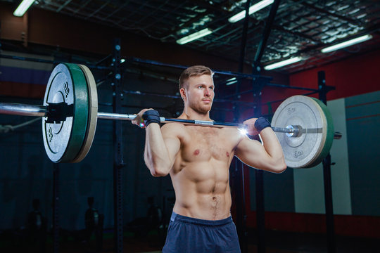 Muscular fitness man preparing to deadlift a barbell over his head in modern fitness center.Functional training.Snatch exercise. Cross style fit, deadlift