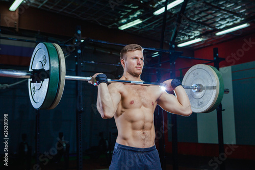 64b6f0e0b818 Muscular fitness man preparing to deadlift a barbell over his head in  modern fitness center.Functional training.Snatch exercise. Cross style fit